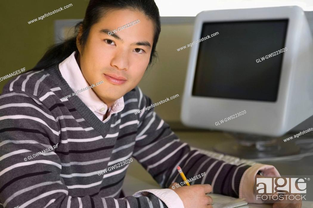 Stock Photo: Portrait of a young man sitting in a computer lab and studying.