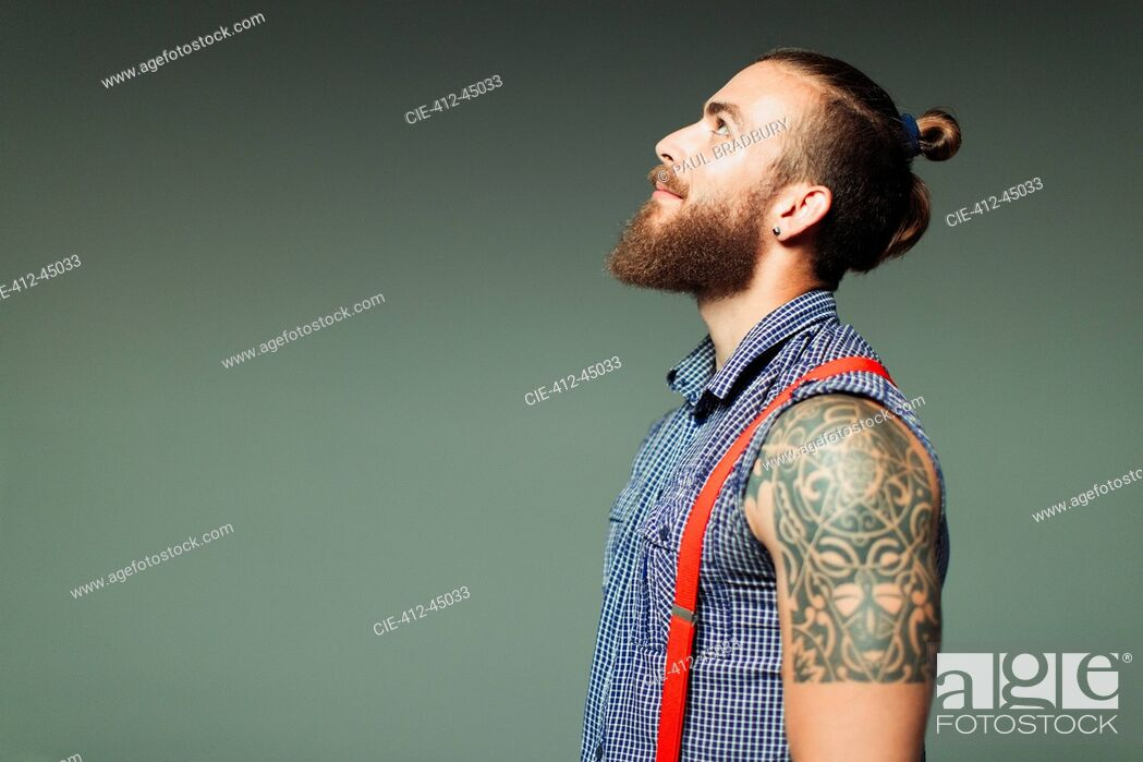 Stock Photo: Curious hipster man with beard and shoulder tattoo looking up.