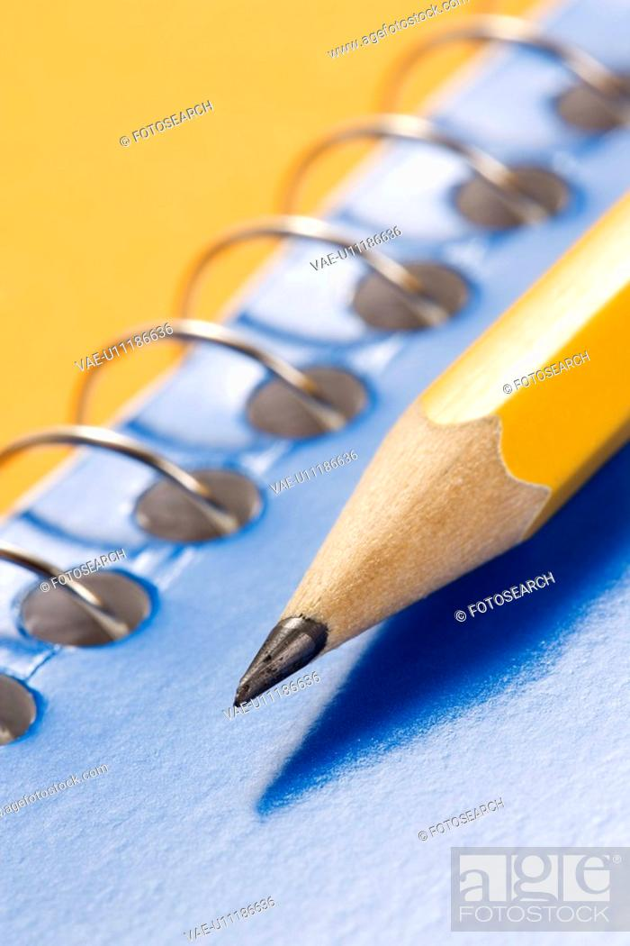 Stock Photo: Close up of sharp pencil placed on blue spiral bound notebook.
