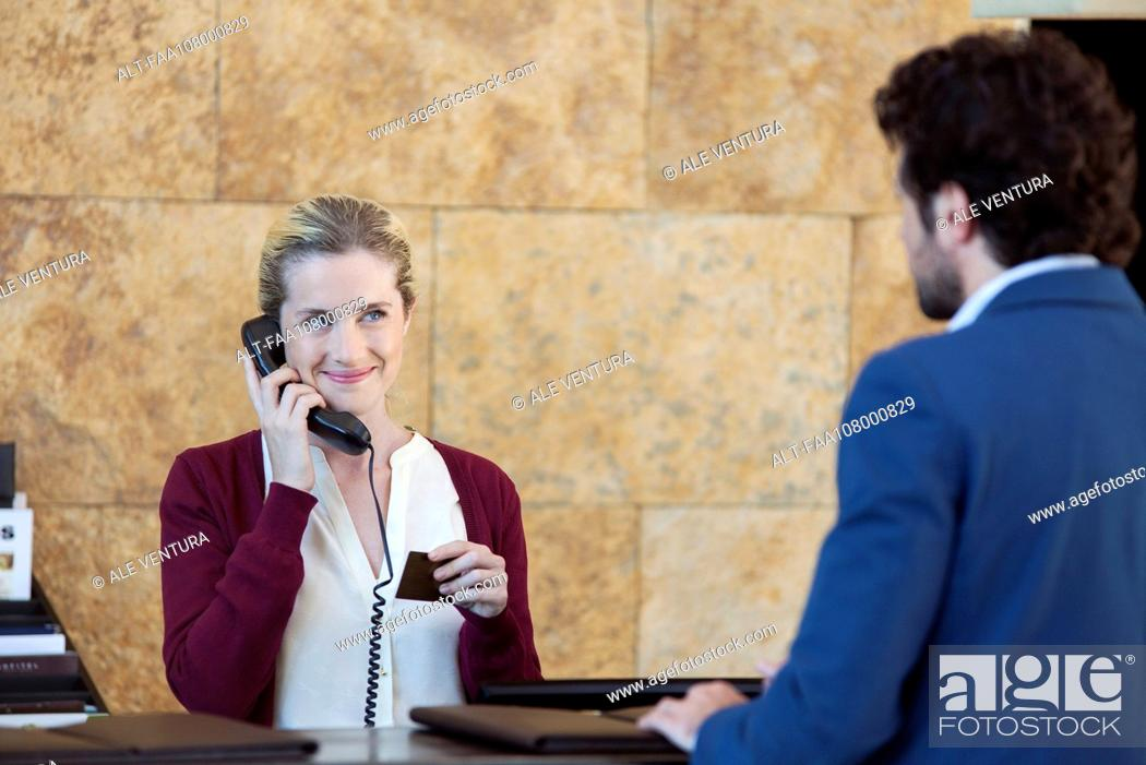 Imagen: Receptionist helping customer while talking on phone.