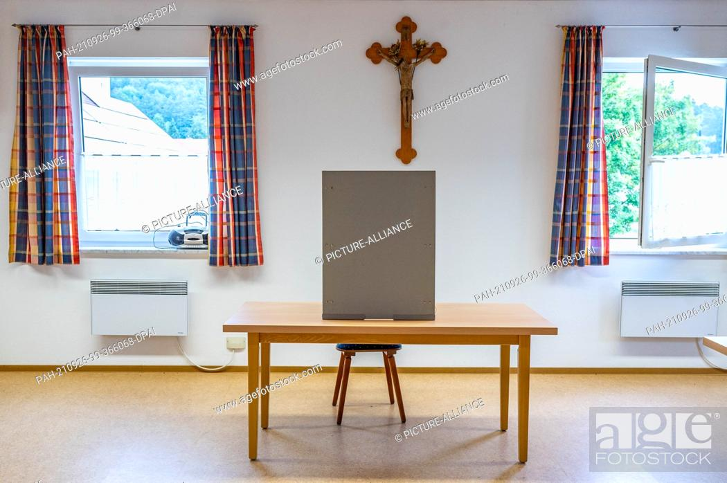 Stock Photo: 26 September 2021, Bavaria, Inkofen: An empty voting booth sits on a table in front of a wooden cross at a polling station. Photo: Armin Weigel/dpa.