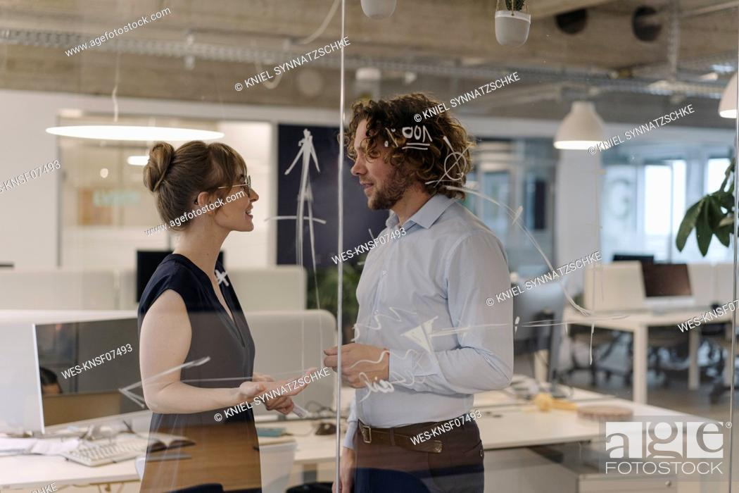 Stock Photo: Businessman and businesswoman working on a project in office.