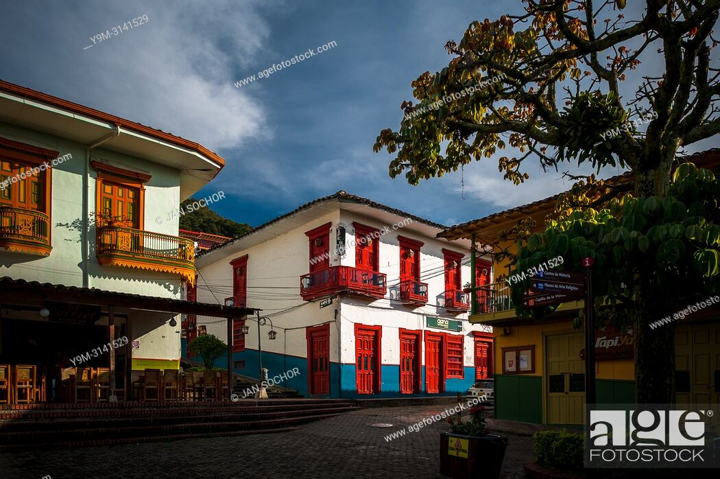 Stock Photo: Brightly painted colonial houses are seen on the main plaza during the sunrise in Jericó, a village in the coffee region (Zona cafetera) of Colombia.
