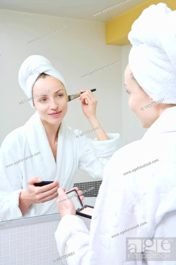 Stock Photo: Young woman using make-up brush.