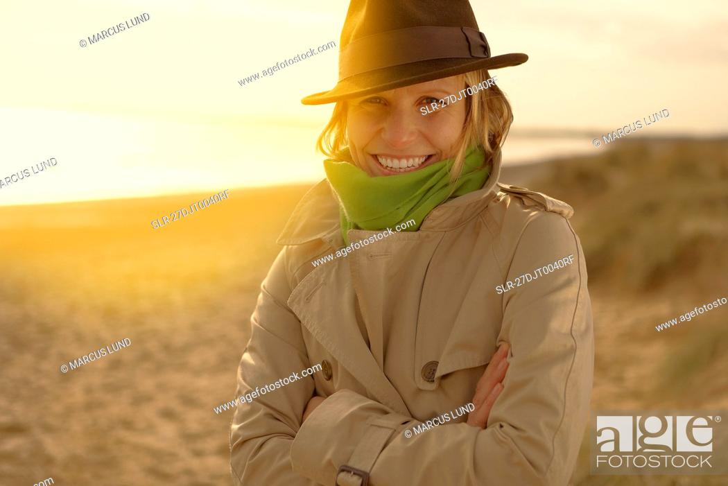 Stock Photo: Young woman on beach in hat and raincoat.