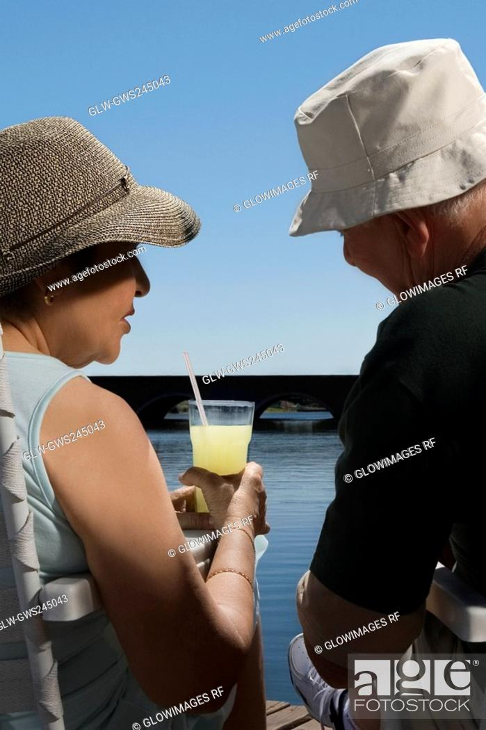 Stock Photo: Rear view of a senior couple sitting at the lakeside.