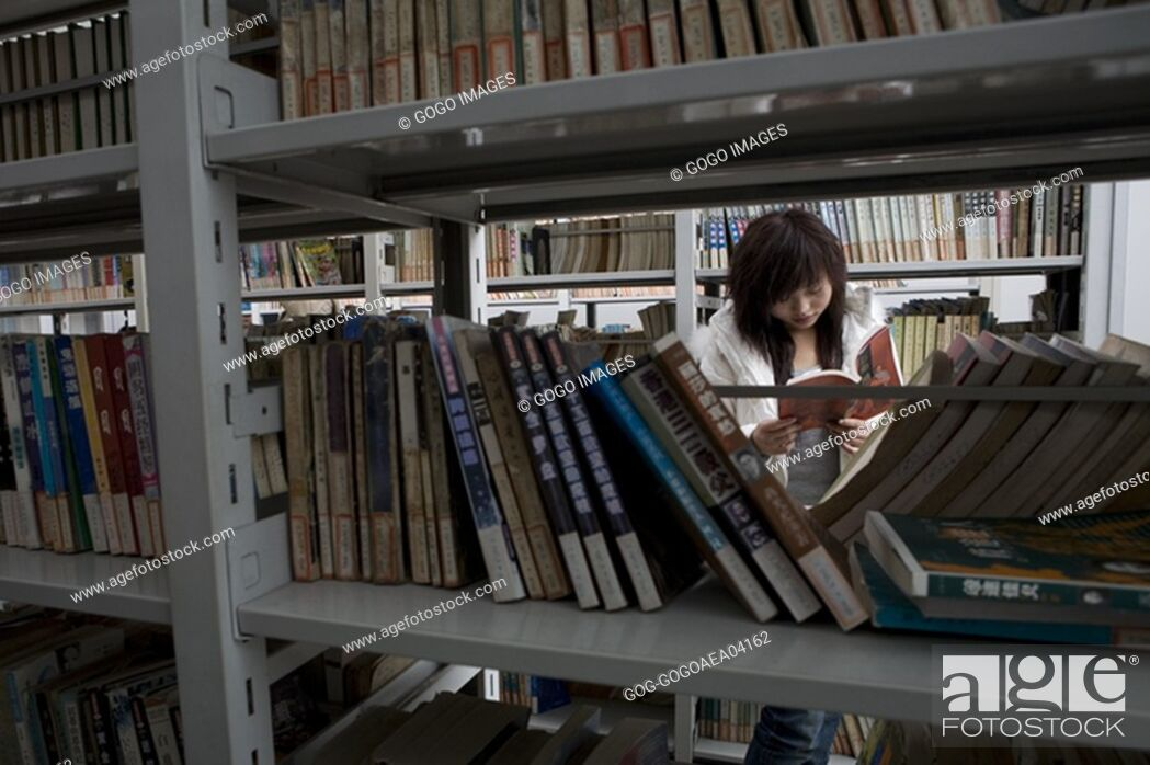 Stock Photo: Man reading book in bookstore.