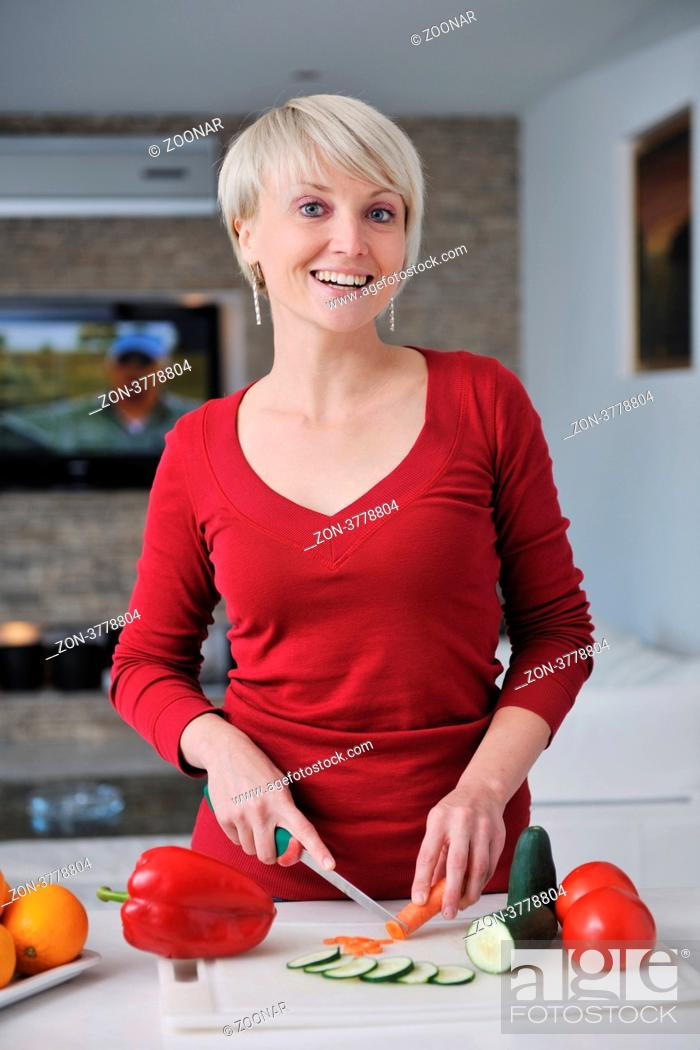 Stock Photo: happy young beautiful blonde woman prepare food in the kitchen at home.