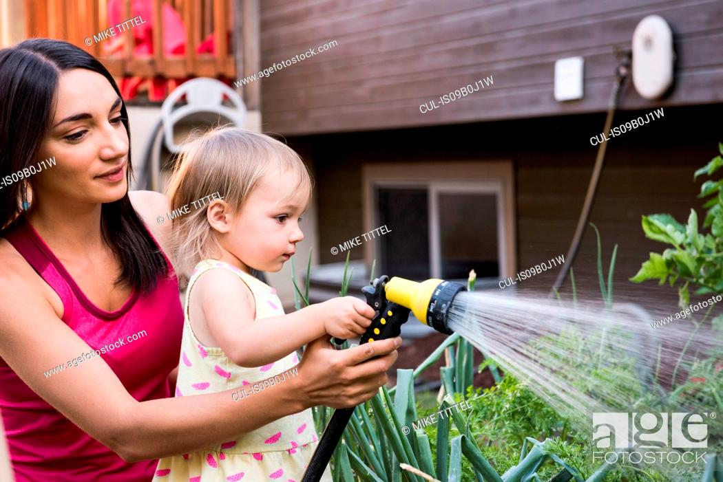 Imagen: Mother and daughter in garden, watering plants together with hose.