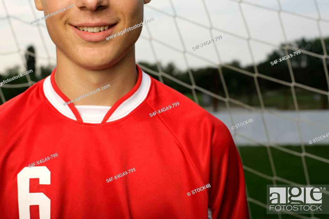 Stock Photo: Soccer player standing in front of a goal.
