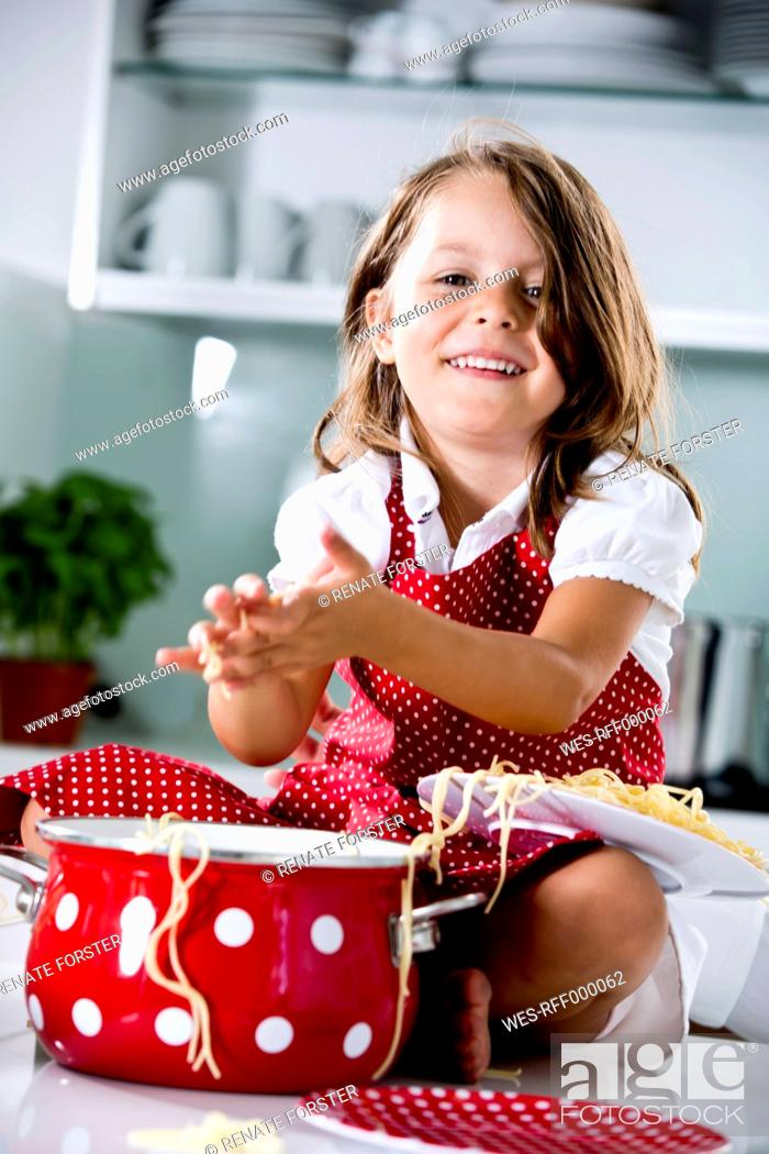 Stock Photo: Germany, Girl playing with spaghetti, smiling, portrait.