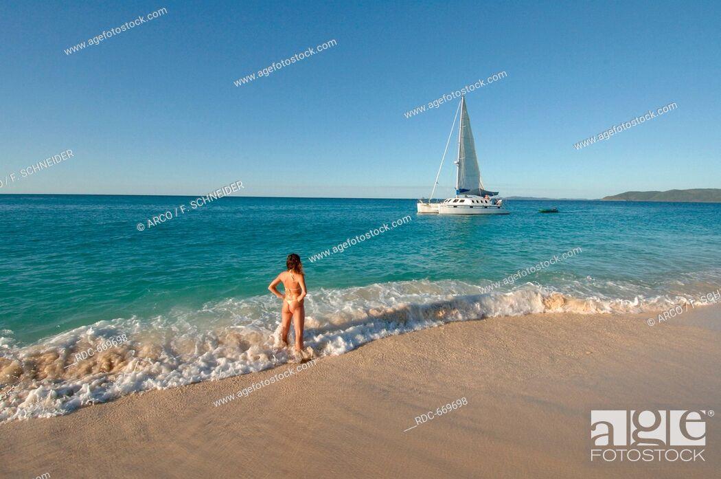 Stock Photo: Woman at beach looks at sailboat, catamaran, travel, vacation, sea, southsea, tropics.