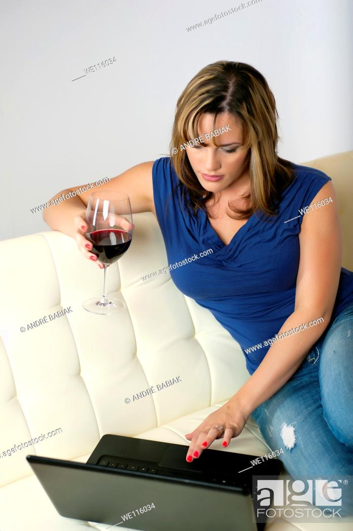 Stock Photo: Woman social networking at home while enjoying a glass of red wine.