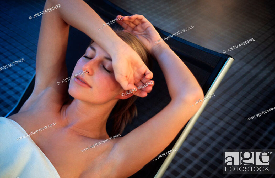 Stock Photo: young woman relaxing, lying, on a deck chair in a rest room, chill-out room of a spa.
