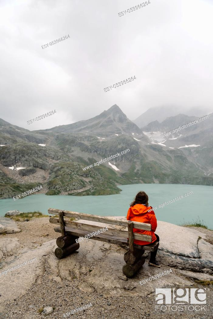 Imagen: Young woman sitting on bench at Alpine lake with space for copy. She is curly and wears casual clothes. Rear view.