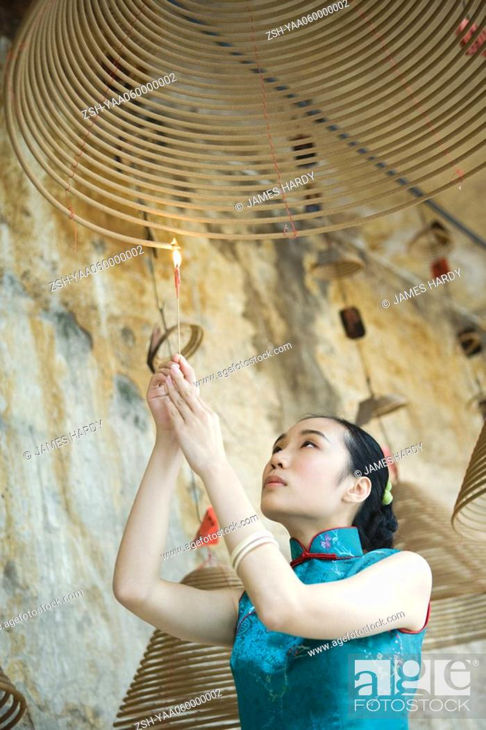 Stock Photo: Young woman dressed in traditional Chinese clothing lighting spiral incense hanging from ceiling, low angle view.