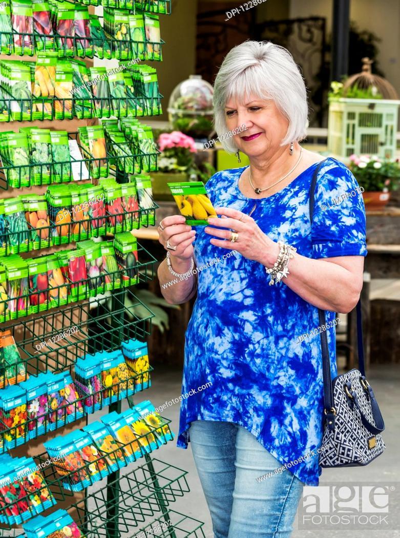 Imagen: Mature woman shopping for garden seeds in a garden centre in a shopping complex; St. Albert, Alberta, Canada.