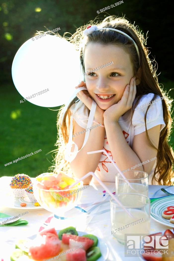 Stock Photo: Girl smiling happily at birthday party.