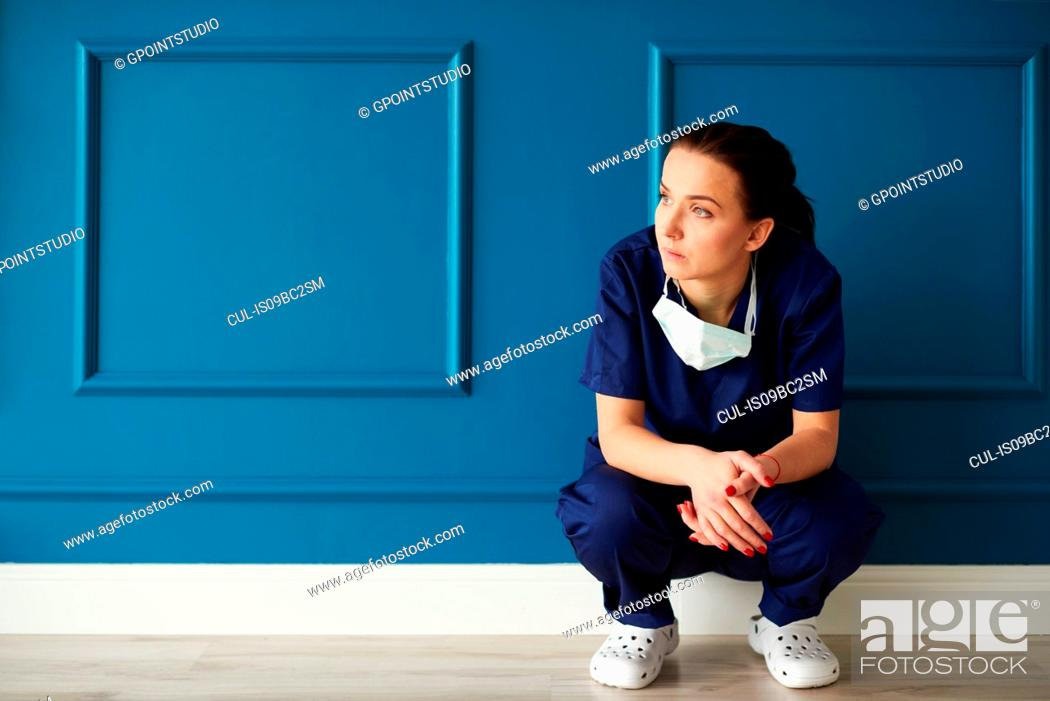 Stock Photo: Portrait of female surgeon, crouching, looking away, pensive expression.