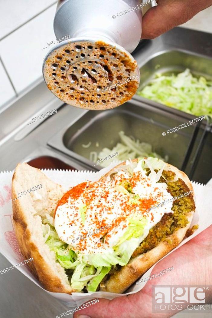 Stock Photo: Adding spicy seasoning to a döner kebab.