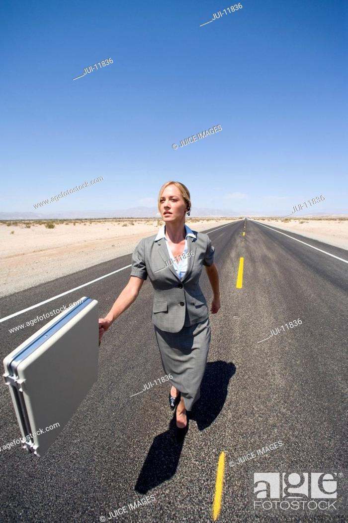 Stock Photo: Businesswoman walking in middle of road in desert with briefcase, elevated view.
