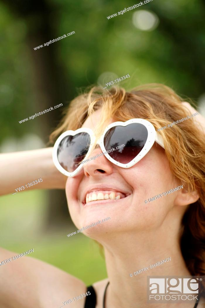 Stock Photo: Portrait of young woman outdoors with heart-shaped sunglasses.