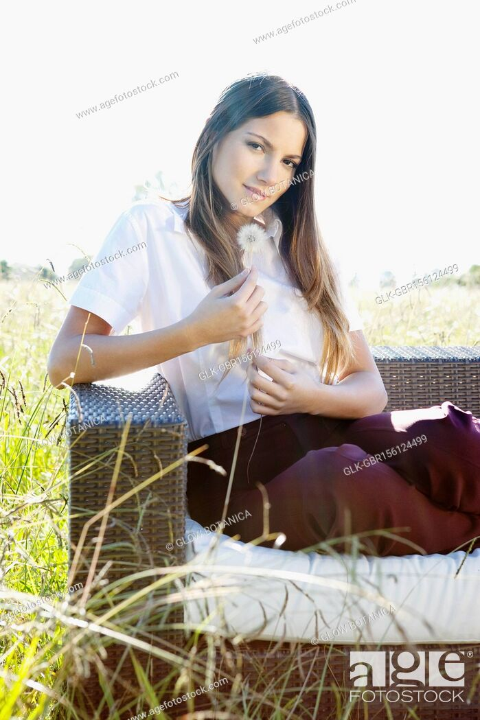 Stock Photo: Businesswoman sitting on a sofa and holding dandelion.