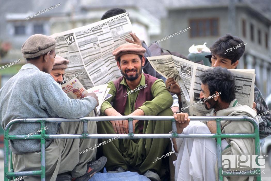 Stock Photo: Pakistan, Baltistan, Skardu, Men reading newpapers on top of a bus.