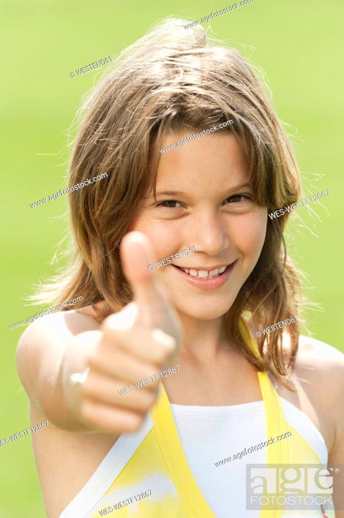 Stock Photo: Girl 10-11 thumbs up, smiling, portrait, close-up.