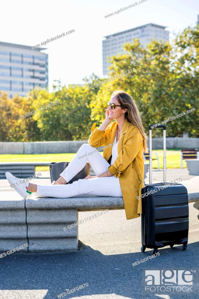 Stock Photo: Smiling woman with suitcase sitting on a bench in the city.