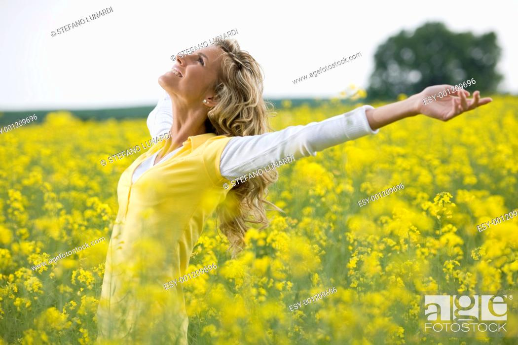 Stock Photo: Beautiful woman in a yellow flowers field with arms outstretched.