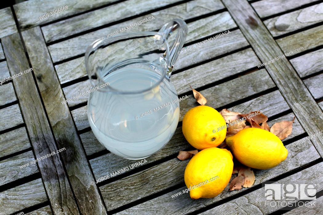 Stock Photo: Lemon juice and lemons on a wooden table.