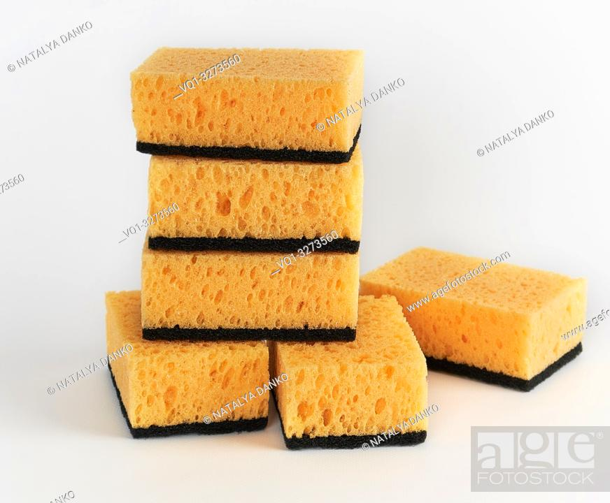 Imagen: stack of yellow kitchen sponges for washing dishes on a white background.