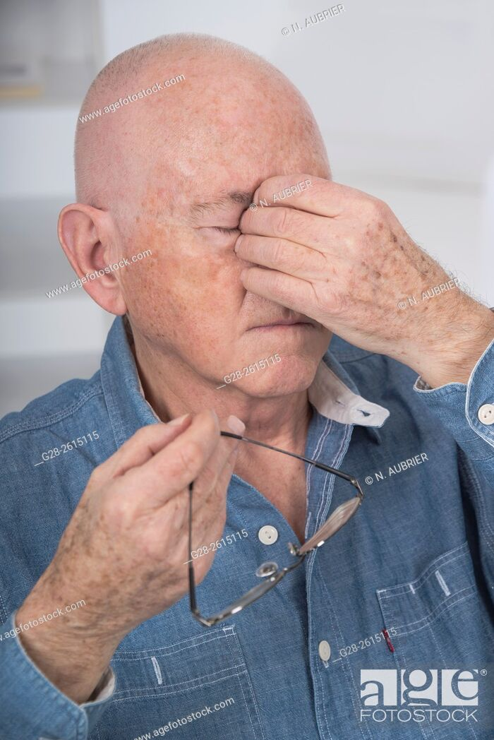 Stock Photo: Senior man with eyes shut, rubbing his eyes because of fatigue or headache, and holding his glasses in one hand.