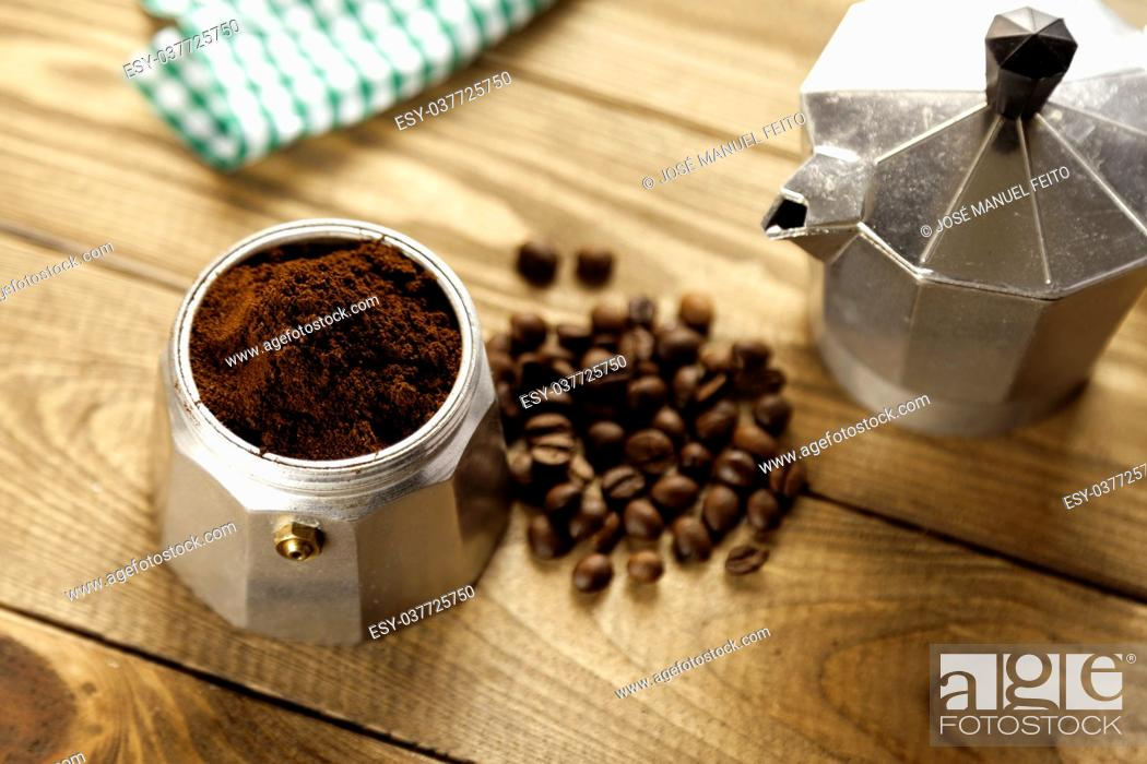 Stock Photo: Italian coffee maker, napkin and coffee beans on wood table.