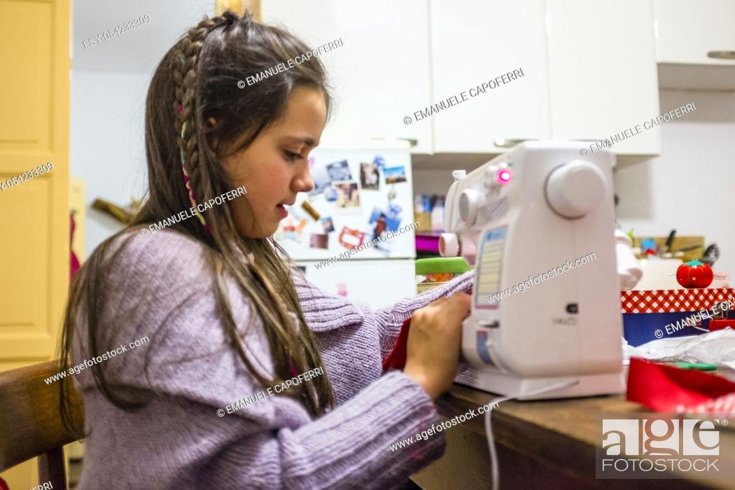 Stock Photo: Child sewing with sewing machine at home.
