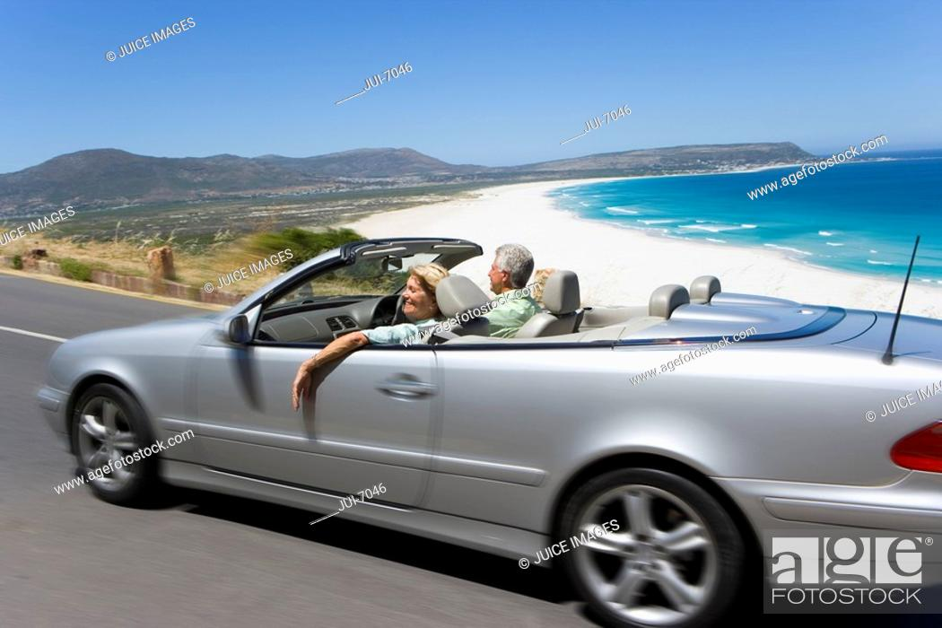 Stock Photo: South Africa, Western Cape, senior couple driving in convertible car along coastal road, smiling, side view blurred motion.