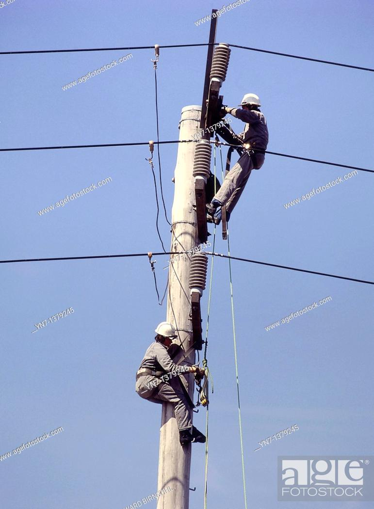 Stock Photo: close view of two linesmen at work up their pole set against a clear blue sky.