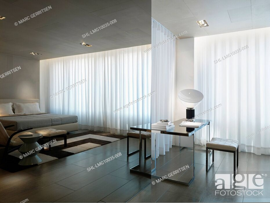 Stock Photo: Interior view of a bedroom with white sheer curtains.