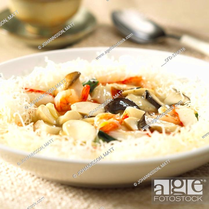 Stock Photo: Seafood and mushroom stir-fry on rice noodles.