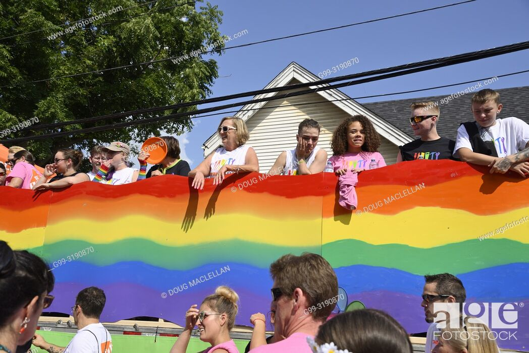 Stock Photo: People standing on a float with a pride rainbow banner and people walking at the annual Pride March, Windsor, Canada.