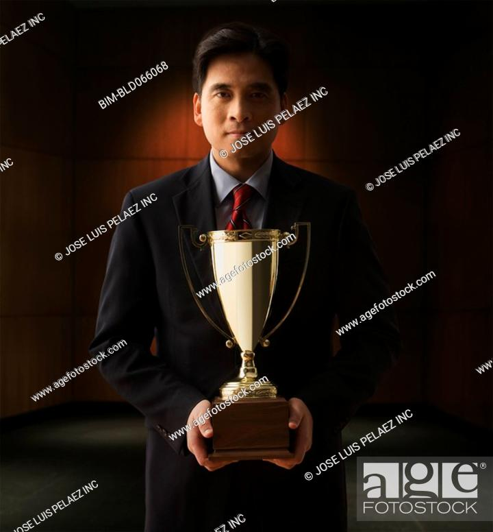 Stock Photo: Chinese businessman holding trophy.