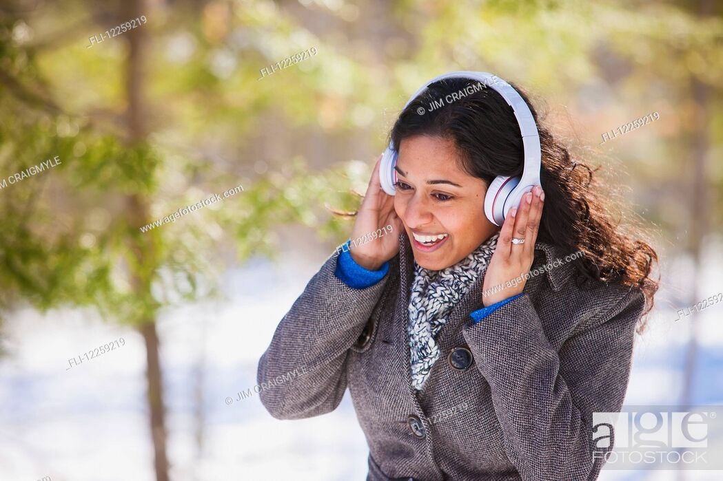 Stock Photo: Young woman of South Asian ethnicity listening to music on Bluetooth headphones in Scanlon Creek Conservation Area; Ontario, Canada.