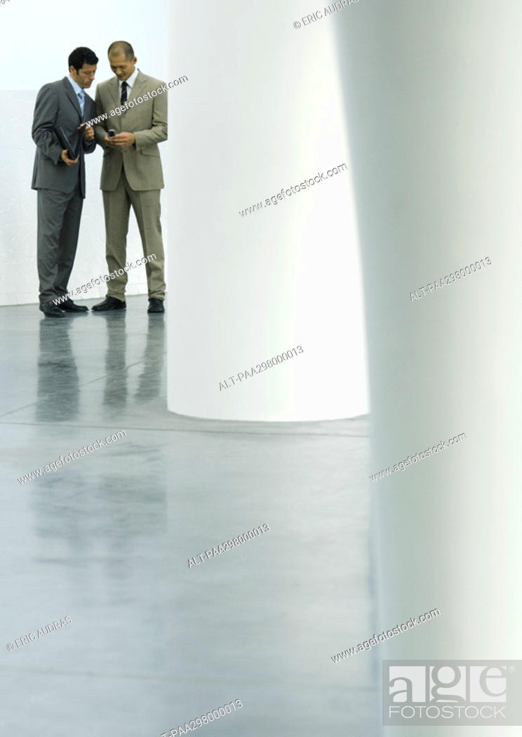 Stock Photo: Two businessmen standing in lobby, looking at cell phone.