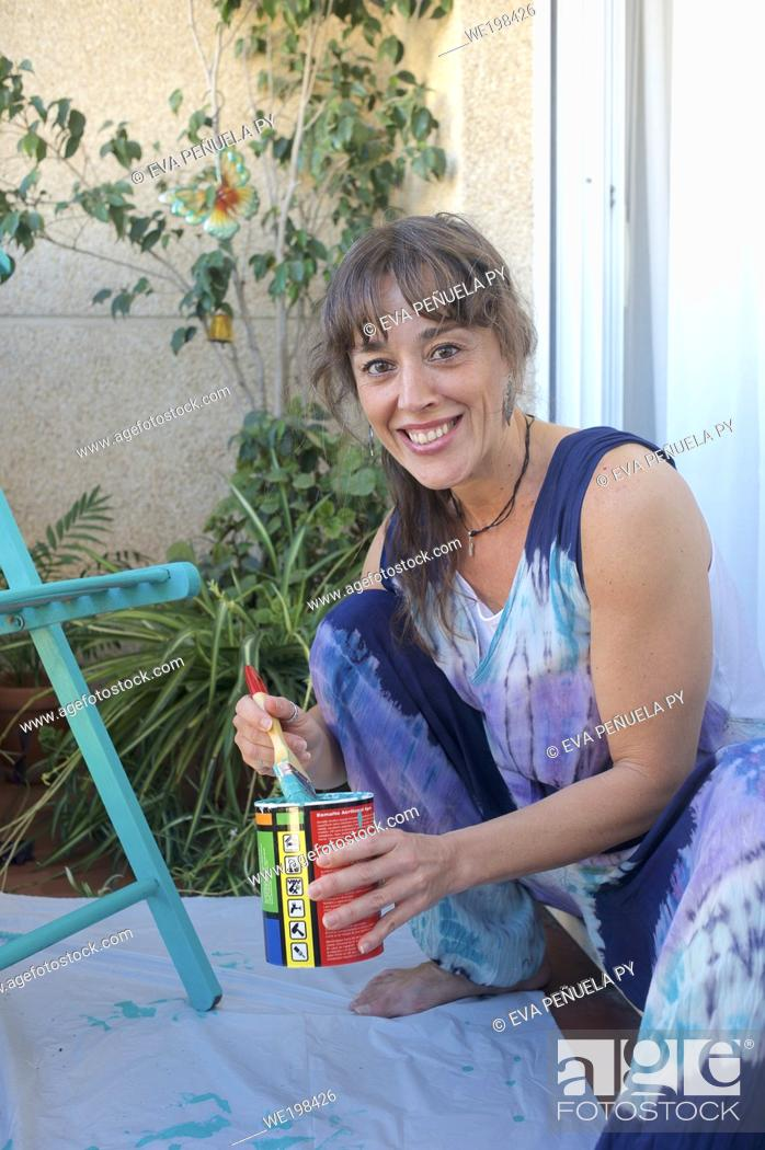 Stock Photo: Young woman painting a chair green on her terrace.