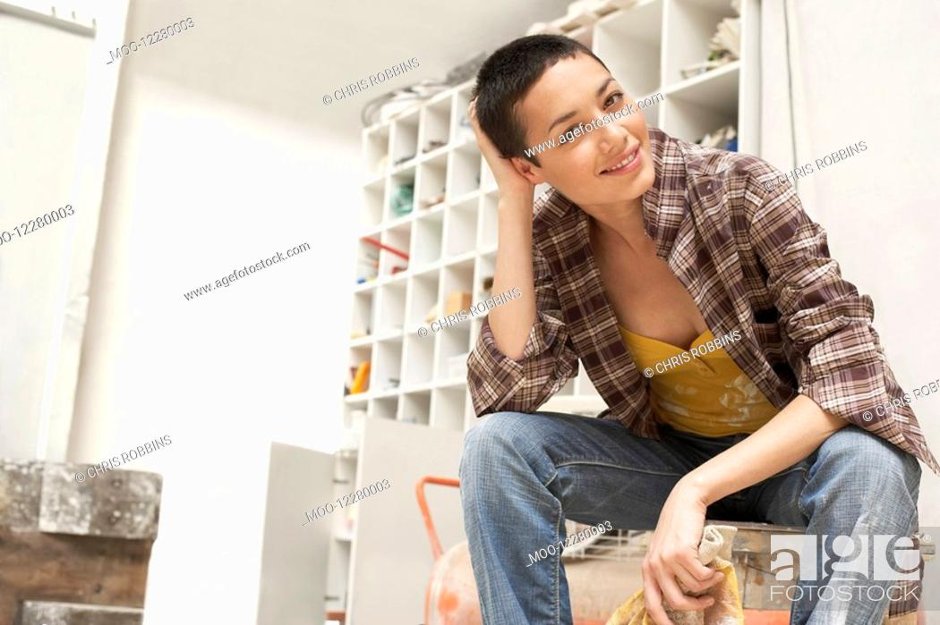 Stock Photo: Female painter on Work Break in tool room portrait low angle view.
