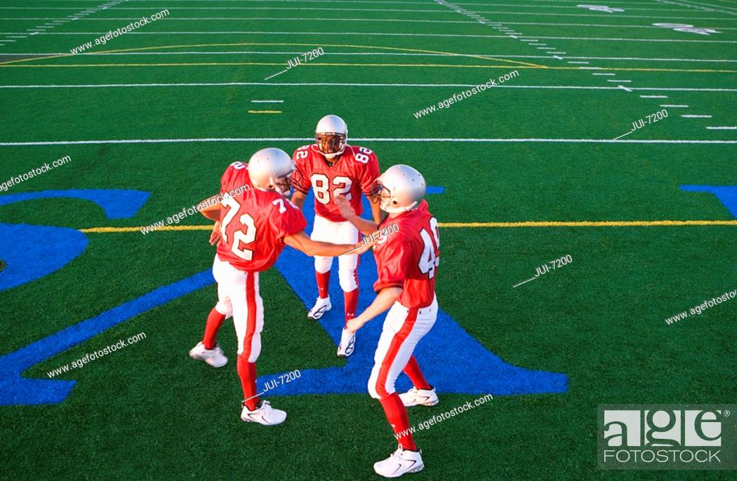 Stock Photo: Two American football players congratulating teammate on pitch during competitive game, elevated view.