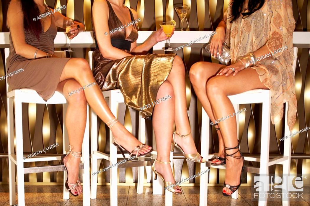 Stock Photo: Stylishly dressed women sitting legs crossed at bar drinking low section.