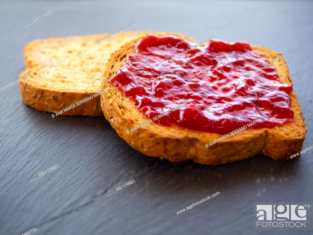 Stock Photo: Two slices of toast with raspberry jam on a slate plate.