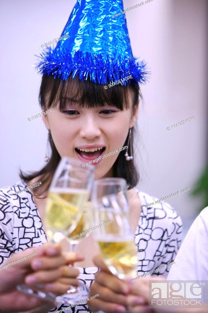 Stock Photo: Young woman wearing headwear and toasting with other people.